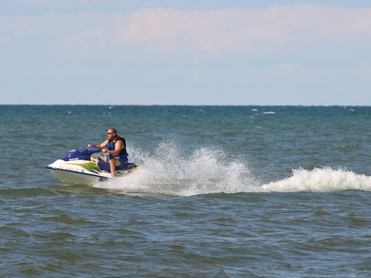 A person on a jet ski along the beach at Edgemere Dr. in Greece and a huge July 4th party.