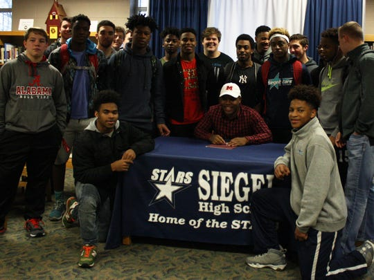 Siegel football standout Rodney Murray recently signed with Maryville College. Pictured are Murray (seated) and Siegel teammates.