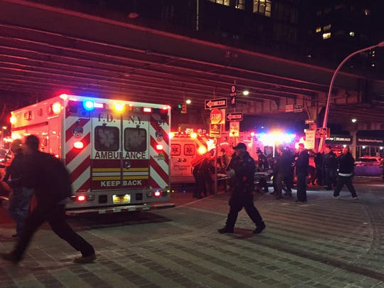 First responders carry a person to an ambulance after a helicopter crashed into the East River along New York on Sunday, March 11, 2018.
