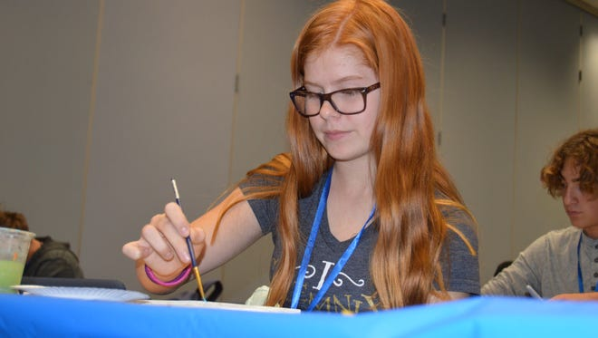 Sophia Litauszki paints a picture of an island as part of the Ventura County Office of Education's Teens Kick Ash event.