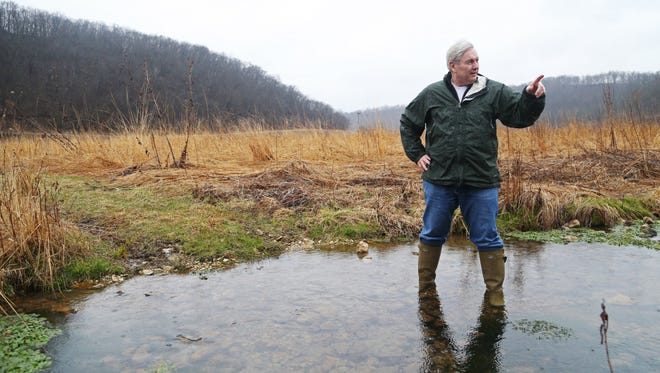 Michael Osterholm, a native Iowan who now lives in Minneapolis, stands in Brook Creek, a cold-water spring-fed creek that Osterholm brought back to life on this property in northern Allamakee County on Monday, April 3, 2017, near Dorchester. When he purchased the property in 2002 a corn field stood where the creek flows and native prairie grasses now grow.