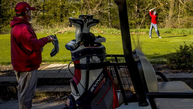 Tim Lane, left, of Peoria, watches his playing partner, Frank Knoll, of Chillicothe, tee off on the first hole on May 1, 2020 at Newman Golf Course in Peoria. Courses around the Peoria area this summer saw growth this summer as people were able to hit the course during the COVID-19 pandemic.