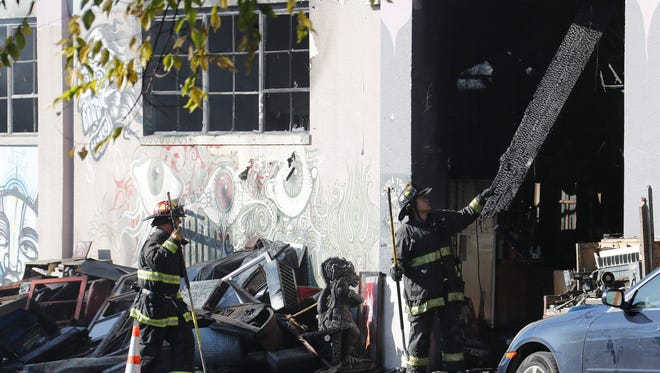 Firefighters work at the aftermath of  the  warehouse fire in Oakland, Calif., Dec. 3, 2016.