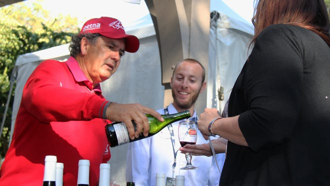 Champions Tour member David Frost gives samples of his wine during the ACE Group Classic Fanfest at TwinEagles Country Club on Friday, Feb. 13, 2015.