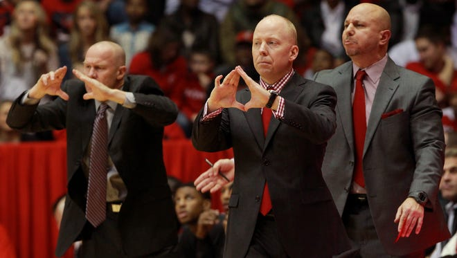 Cincinnati head coach Mick Cronin, middle, gestures to his team during a game against Memphis in March.
