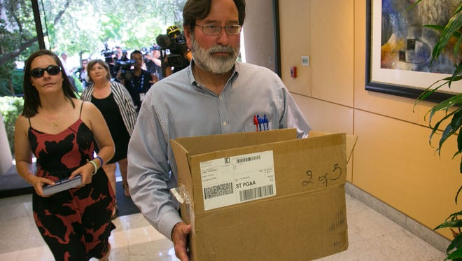 """Richard Martinez, father of a UCSB shooting victim, arrives at Sen. Jeff Flake's office with postcards reading, """"Not one more."""""""