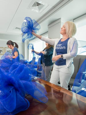 Monique Brown checks out her handy work as she and fellow employees make big blue bows for the Gulf Coast Kid's House's Blue to Better campaign at Envision in Pensacola on Thursday, March 22, 2018.