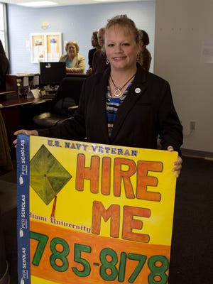Veteran Marianne Linardos shows her HIRE ME sign at the SuperJobs center in 2013.