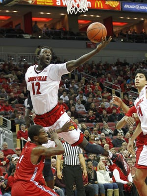 University of Louisville's Mangok Mathiang (12) fights to get his shot off under pressure from Jacksonville State's Avery Moore (1) during the second half at the KFC Yum! Center in Louisville, Kentucky.       November 17, 2014