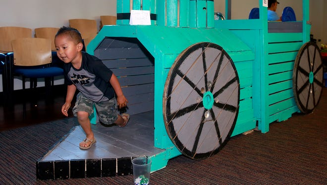 Adam Yazzie, 4, explores a train built by Chandra Lopez, her son, Quintano Charley, 14, and other family members at the Pallet Throwdown on Saturday at the Farmington Public Library.