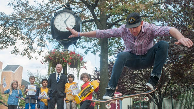 Collingswood Mayor Jim Maley and neighborhood children watch as professional skateboarder Ronnie Gordon performs a skateboard trick  on Haddon Ave. in Collingswood. Gordon owns Metropia Skateboards, and will giving away a skateboard to the winner of an essay contest Wednesday at the Pop Shop.