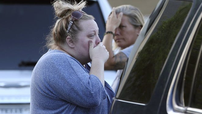 Marilee White, left, with sister Jaime White react outside First Baptist Church in New Braunfels, Texas, after several people who attended the church died in a two vehicle collision Wednesday, March 29, 2017. It was not immediately clear what caused the deadly crash involving a van carrying church members and a pickup truck on U.S. 83 outside Garner State Park in northern Uvalde County, Texas. (Tom Reel/The San Antonio Express-News via AP)
