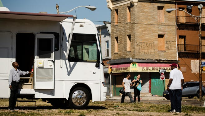 Alfred Gibson, left, and Wesley Anderson Jr., right, set up the Camden Area Health Education Center Mobile Health Van in a vacant lot where people can access counseling and testing in Camden, N.J.