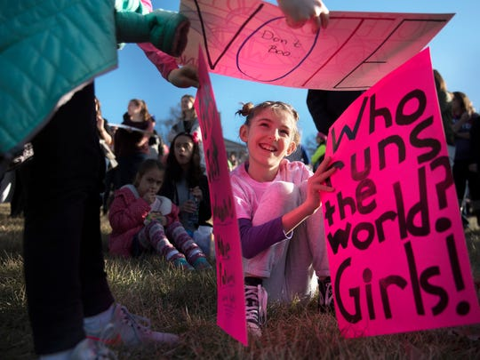 Opal Ivester, 9, of Nashville, smiles as she helps 9-year-old Betsy Hart Wright, of Nashville, build a house from signs they carried Saturday, Jan. 20, 2018, during the Women's March in Nashville.