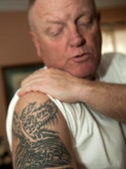 Army Lt. Col. John Hodson shows a tattoo in remembrance of members of his unit that were killed when their Black Hawk helicopter was shot down in Baghdad, Iraq in January 2007. Hodson was in Oaklyn visiting his father, John Hodson Sr. after returning recently from a tour of duty in Afghanistan.
