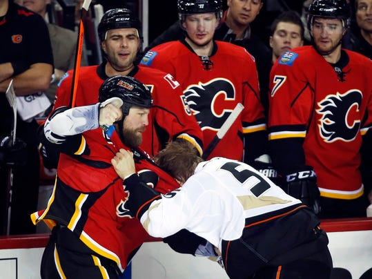 Anaheim Ducks' Bryan Allen, right, fights with Calgary Flames' Brian Mcgrattan during the first period of an NHL hockey game in Calgary, Alberta, Wednesday, March 12, 2014. (AP Photo/The Canadian Press, Jeff McIntosh)