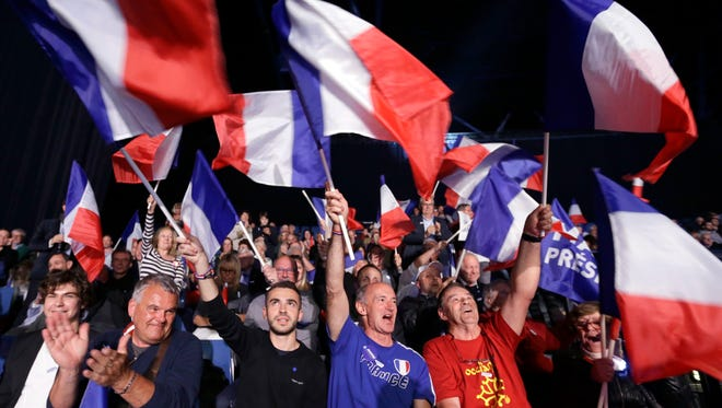 """Supporters wave French flags prior to an election campaign rally of French far-right leader and presidential candidate Marine Le Pen in Nice, southern France, Thursday. After """"the battle of Whirlpool,"""" when Marine Le Pen and Emmanuel Macron both went hunting for France's blue-collar vote at a threatened home appliance factory, the presidential candidates clashed over fish as Le Pen boarded a fishing trawler, in a return to more traditional campaigning. (AP Photo/Claude Paris)"""