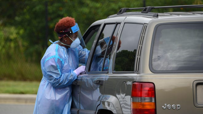 A nurse from the Alamance County Health Department reaches into a Jeep to conduct the nose swab for a COVID-19 test.