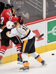 Nashville Predators defenseman Ryan Ellis (4) and Chicago Blackhawks center Tanner Kero (67) tussle along the boards in the third period of game two in the first-round NHL playoff series at the United Center, Saturday, April 15, 2017, in Chicago, Ill.