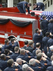 Firefighters stand in salute as the casket carrying Chris Blankenship, a 10-year veteran of the Madison County Fire Department, is loaded onto a fire truck after his funeral at the Civic Center.