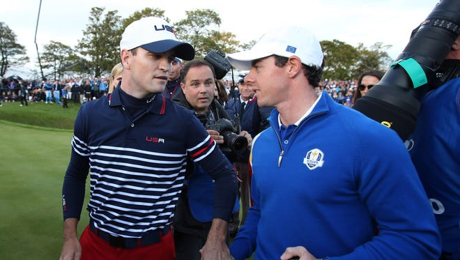 European player Rory McIlroy, right, shakes hands and apologizes to USA player Zach Johnson on the 18th green for popping the cork on the champagne while Johnson was putting on the last match of day three during the 2014 Ryder Cup.