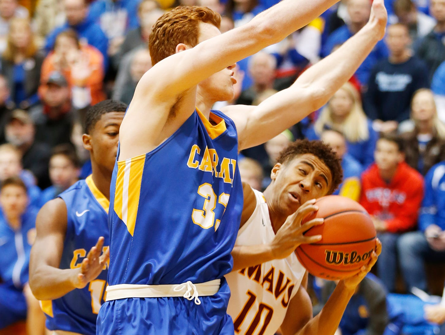 Carmel's John Michael Mulloy blocks the path of McCutcheon's Robert Phinisee in the Greyhounds' regional semifinal win at Logansport. Carmel lost in the final to Fort Wayne North Side.