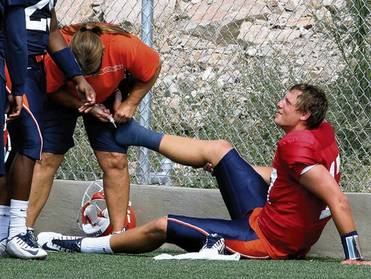 A UTEP trainer cuts off quarterback Garrett Simpson's sock after he injured his foot while jumping into receiver Cole Freytag to celebrate a touchdown pass during Saturday's scrimmage at Glory Field.
