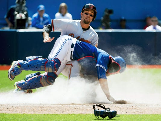 Baltimore shortstop J.J. Hardy, back, slides safe at home plate past Toronto catcher Russell Martin, front, during the ninth inning of Saturay's game in Toronto. The Orioles won, 5-3, to end the Blue Jays' home winning streak.