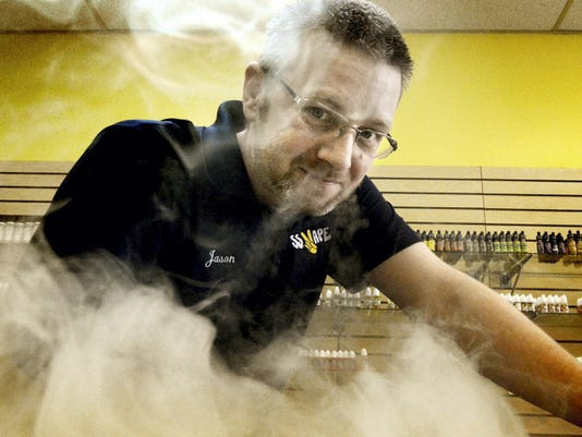 SS Vapes District Manager Jason Goins exhales a cloud of vapor at the Manchester Crossroads Shopping Center store.