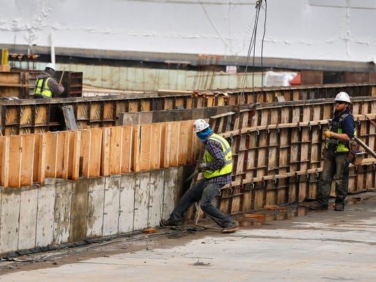 A construction crew works on concrete forms at the