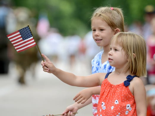 Grace Brown, 3, of Fort Collins, waves her American flag during the Independence Day Parade along Mountain Ave. in Fort Collins July 4, 2014.