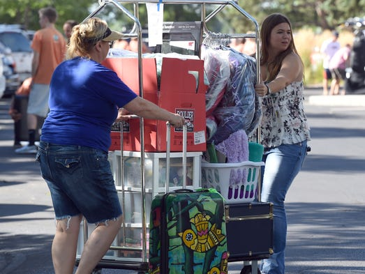Beata Cole, left, of Los Angeles, helps her daughter, Brianna, 18, with her belongings during the move-in day for incoming freshman Thursday Aug. 21, 2014. Brianna plans to major in equine science.