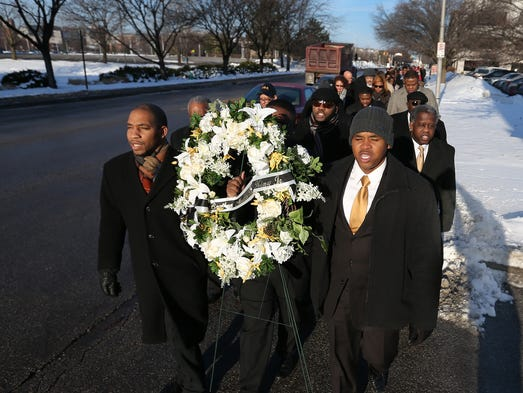 "Kendrick Tunstall (left), Davyd Hall (behind wreath) and Edgar Holmes III (right), members of the Alpha Phi Alpha Fraternity, participate in the ""Freedom Walk"" along Indiana Avenue on Martin Luther King Jr. Day, Jan. 20, 2014, in Indianapolis. They walked to the Madame Walker Theatre Center."
