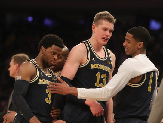 Michigan's Zavier Simpson, Moritz Wagner and Charles Matthews cheer from the bench during the final seconds of their Big Ten tournament game against Nebraska on March 2, 2018.