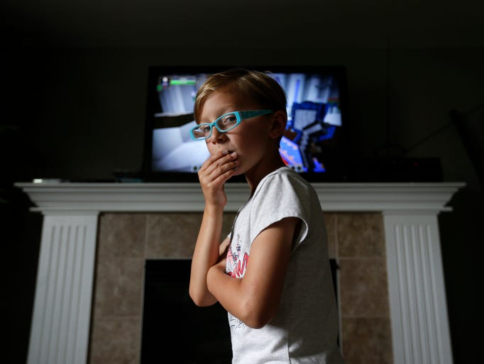 Ryland Kelting, 9, watches TV with his siblings Saturday,