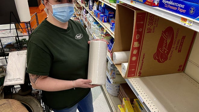 Amy Oliveira, general manager for Auclair's Market in Somerset, holds an off-brand roll of paper towels she sells when she can't get the name brand product in stock.