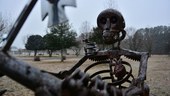A sculpture of a skeleton stands outside the Hagen studio on Route 24. The yard is covered in recycled art, from mermaids to dragons, and metal giraffes hiding in the foliage.