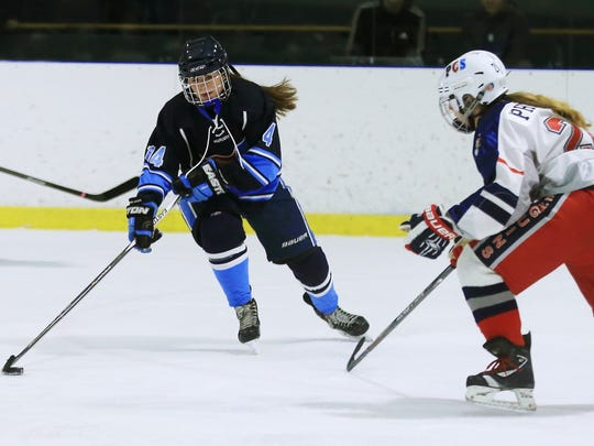Looking to snap a shot is Livonia Ladywood's Sydney Malek (24). At right for the PCS Penguins is defenseman Alexis Pheeney.