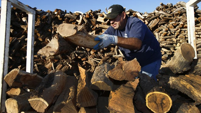 pni0104-no burn day 0104121141dp -- 1/4/2012 -- Jose Hemes (cq) stacks wood at Paul Bunyan's Firewood in Guadelupe, AZ. Rob Schumacher/The Arizona Republic