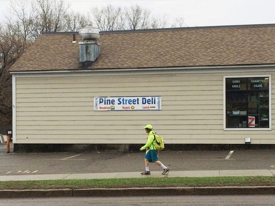 Jane Hendley walks past the Pine Street Deli in Burlington on Friday, en route to her work at University of Vermont