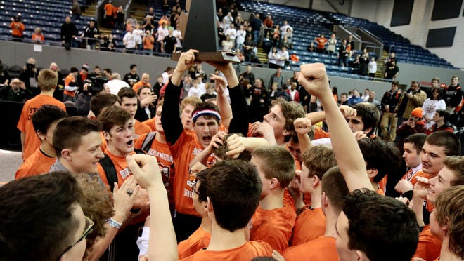 Brighton's Nick Brish hoists the Division 1 state championship trophy after the Bulldogs edged Hartland to win its first title in school history.