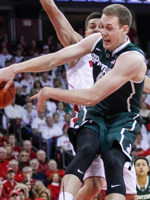 Michigan State's Colby Wollenman, front, passes against Wisconsin's Bronson Koenig on Sunday, March 1, 2015, in Madison, Wis.