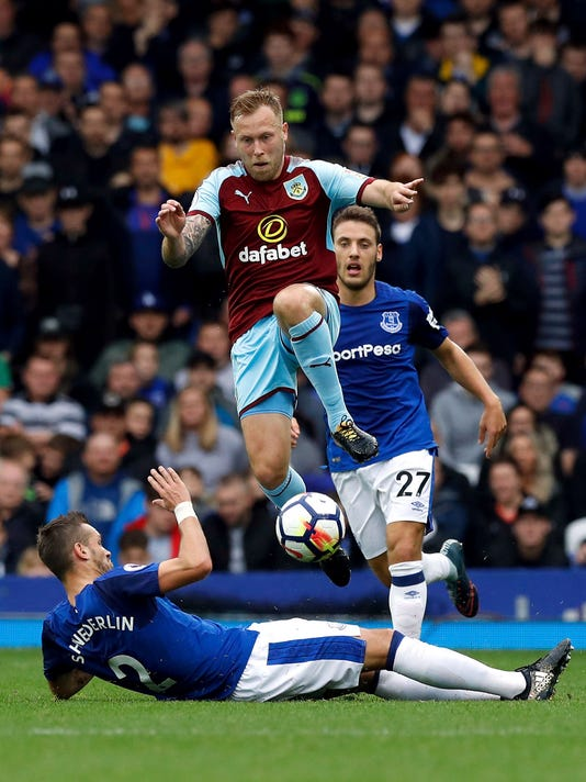 Burnley's Scott Arfield skips over the tackle from Everton's Morgan Schneiderlin during the English Premier League soccer match at Goodison Park in Liverpool, England, Sunday Oct. 1, 2017.  (Martin Rickett/PA via AP)