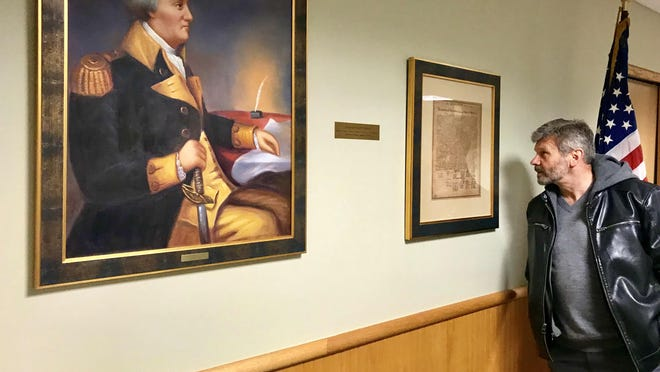 D. Allan Kerr views a portrait of Gen. William Whipple Kittery Town Hall which hangs next to a copy of the Declaration of Independance, which the general signed.