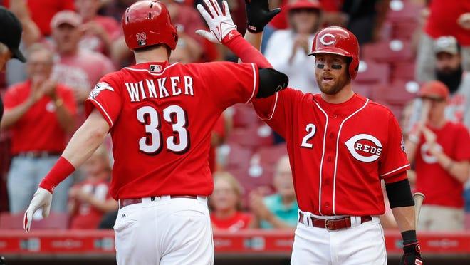 Cincinnati Reds' Jesse Winker (33) celebrates with Zack Cozart (2) after hitting a solo home run off Pittsburgh Pirates starting pitcher Ivan Nova in the seventh inning of a baseball game, Saturday, Sept. 16, 2017, in Cincinnati. (AP Photo/John Minchillo)