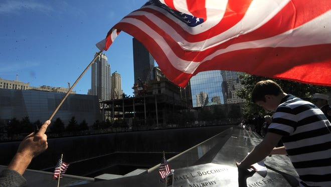 An American flag is waved at the World Trade Center memorial site in New York City.