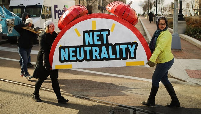Rally organizers carry away props following a protest outside the Federal Communication Commission building against the end of net neutralityrules December 14, 2017 in Washington, DC.