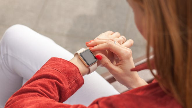 young woman use smartwatch with blank screen outdoor, view of shoulder