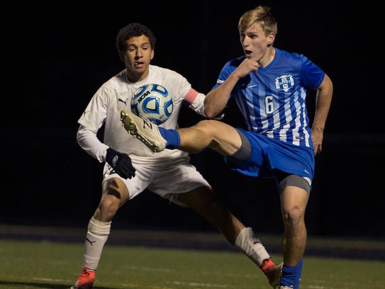 Homdel's Justin McStay works to kick ball over his