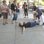 Joyce Fisher, right, uses chalk to outline the torso of Margaret Bigham on the sidewalk under the marquee of the Historic Howell Theater, part of the Pub Crawl activities. Both women are employees at the Howell Carnegie District Library, and put Bigham's outline next to Nancy Aittama's, a fellow employee, who started the trend.